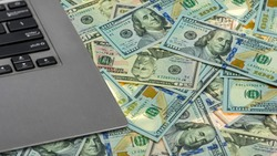 Close-up of a laptop on US dollars in USD 50 and 100 banknotes. Earned money by working from laptop at home. Freelance work making money concept