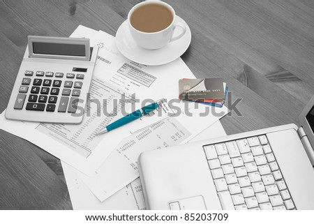 Close up of a laptop with bank and credit card statements and a pile of credit cards with a cup of hot coffee