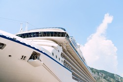 Close-up of a large white moored cruise liner on a jetty near the old town of Kotor in Montenegro.