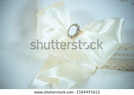 Close-up of a large white silly ribbon with a delicate cameo brooch covering a white bohemian summer hat, vintage accessory for a special occasion, a wedding reception or a period themed garden party #1584495652