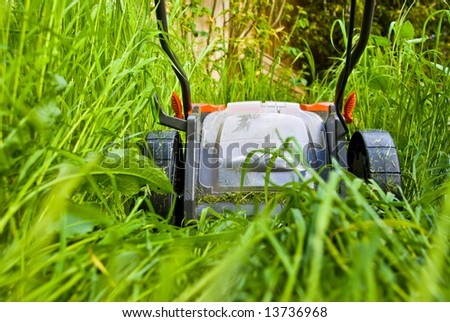 Close-up of a lawnmower cutting long grass