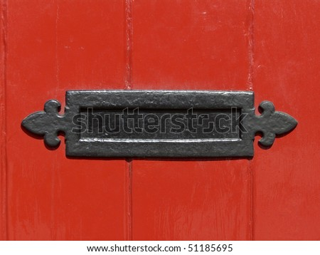 Close up of a letter box in a red door