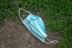 Close up of a light blue doctors face mask or covering with elastic bands laying discarded and littering a parkway in a patch of dirt surrounded by green grass in Chicago.