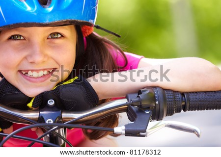 Close-up of a little girl?s face on bike looking at camera and smiling