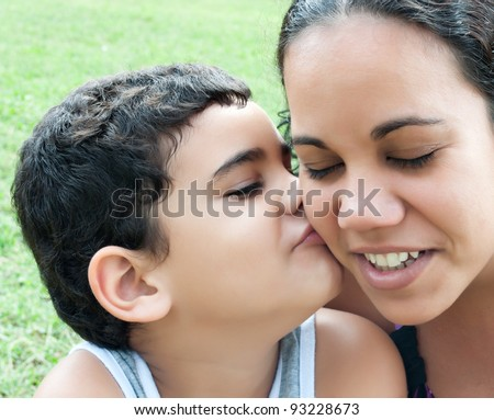 Close up of a little hispanic boy kissing their mother