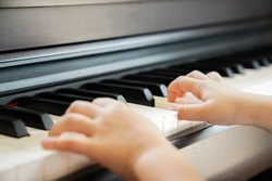 Close up of a little student's hands is playing, learning and practicing the piano. Piano chords In the key of C major. Music abilities for kids. Hobby and activity for the children. Selective focus.