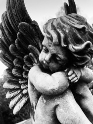 Close up of a little weathered angel statue on a grave stone. Black and white photo.