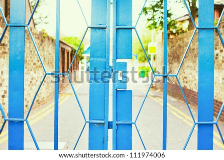 Close up of a locked blue metal school gate
