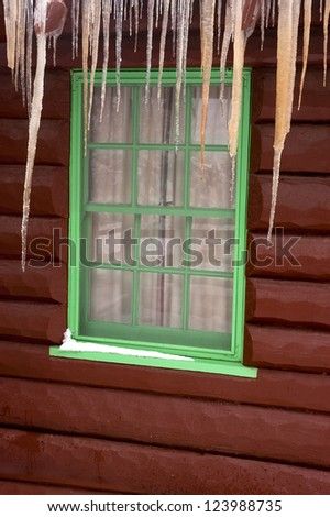 Close up of a log cabin window with icicles hanging from the roof over the window
