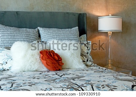 Close up of a luxury set of bedding in black and white patterns with a red accent flower on a bed in natural light
