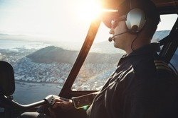Close up of a male helicopter pilot flying aircraft over the Cape town city on a bright sunny day.