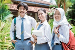 close up of a male Indonesian high school student and two female high school students wearing a school bag and smiling with the camera