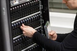 Close-up of a Male IT Technician Analyzing SAN in Datacenter