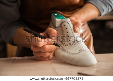 Close up of a male shoemaker drawing design on a new shoes at his workshop
