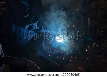 Close up of a male welder in blue uniform, welding mask and welders leathers, weld metal with an arc welding machine at the construction site, blue sparks fly to the sides #1202050465