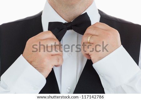 close-up of a man adjusting his bow tie