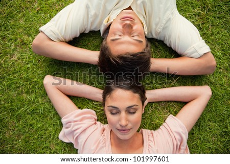 Close-up of a man and a woman with their eyes closed lying head to head with both of their arms resting behind their neck on the grass
