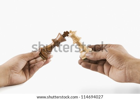 Close-up of a man and woman's hands holding chess king and queen