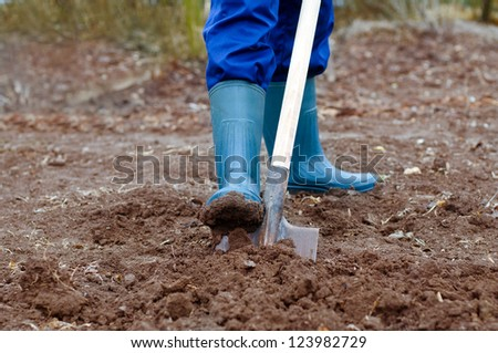 Close up of a man digging soil with shovel in rubber boots and gloves