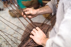 Close up of a man doing basketwork, wickerwork. Basketery. Wicker is a technique for making products woven from any one of a variety of cane-like materials. Traditionally made of material of willow.