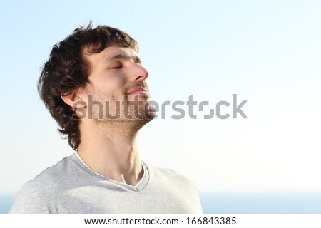 Close up of a man doing breath exercises outdoor with the sky in the background