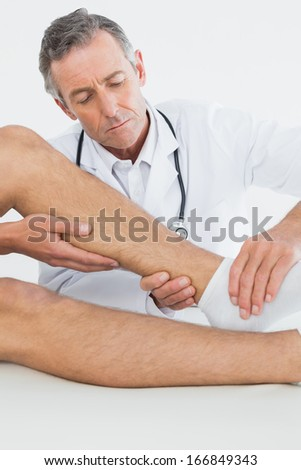 Close-up of a man getting his ankle examined at the medical office