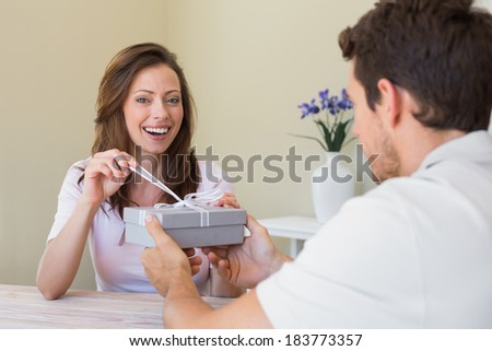 Close-up of a man giving happy woman a gift box at home