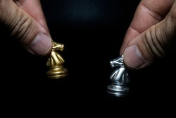 Close-up of a man holding a golden and silver chess horse on a chessboard, copying spaces for your message.