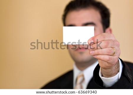 Close up of a man holding an empty business card up.  Plenty of copy space for your logo or design.  Shallow depth of field.