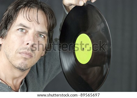 Close-up of a man holding an LP up about to drop it.