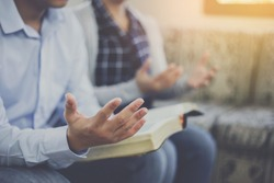 Close up of a man holding bible and raise hand up  praying to God with his friends while sitting on sofa at home, Christian family worship concept, copy space