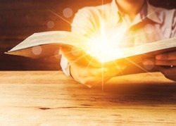 Close Up Of A Man Holding Holy Bible With Star and Bokeh Light Effected on Wood table. Copy space. Christian Background Power Of the word of God Concept.