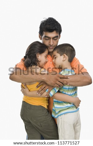 Close-up of a man hugging his children