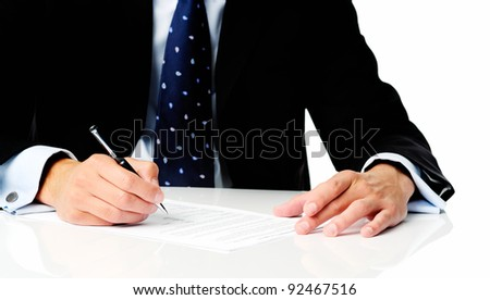 Close up of a man in a suit holding a pen and signing some documents