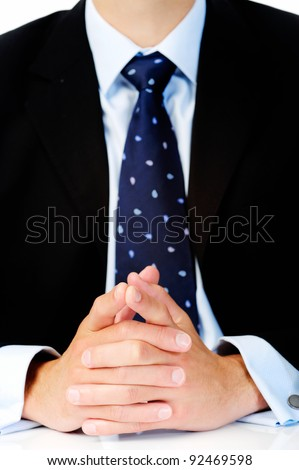 Close up of a man in a suit with his hands clasped in front of him