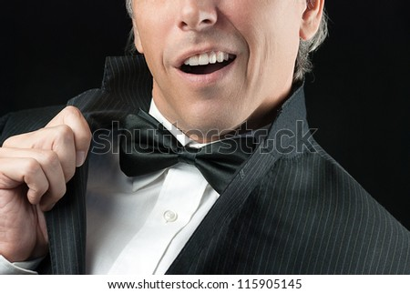 Close-up of a man in a tux doing an Elvis impression.