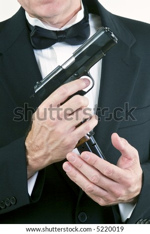 Close up of a man in formal attire, loading his automatic weapon taken agains a white background.