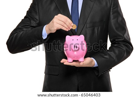 Close up of a man inserting a coin into a piggy bank isolated on white background