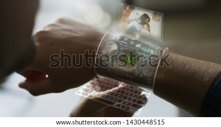 Close up of a man is using futuristic  armband liquid crystals smart watch  with the latest advanced augmented reality holographic technology for call his wife and daughter. #1430448515