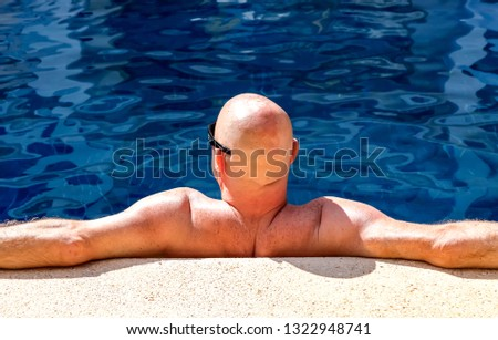 Close up of a man leaning against a poolside edge suntanning and wearing sunglasses. #1322948741