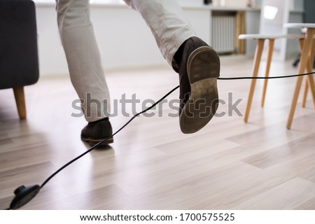 Close-up Of A Man Legs Stumbling With An Electrical Cord At Home Zdjęcia stock ©