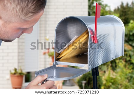 Close-up Of A Man Looking Inside The Silver Mailbox #725071210