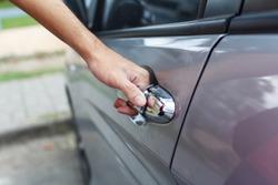Close up of a man opens car's door.