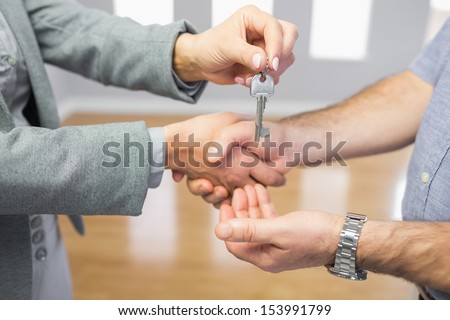 Close up of a man receiving a handshake and a key at the same time