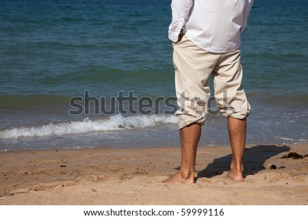 Close up of a man's feet on the sea shore wearing casual clothes
