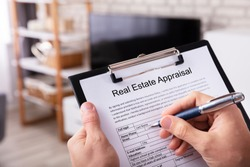 Close-up Of A Man's Hand Filling Real Estate Appraisal Form At Home