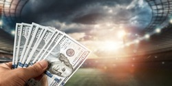 Close-up of a man's hand holding US dollars against the background of the stadium. The concept of sports betting, making a profit from betting, gambling. American football