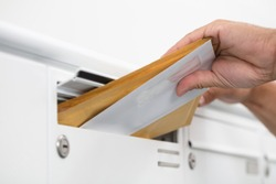 Close-up of a man's hand inserting letters in mailbox