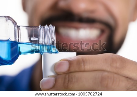 Close-up Of A Man's Hand Pouring Mouthwash Into Cap