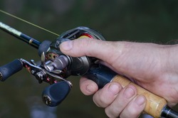 Close-up of a man's hand with bait casting rods. Caucasian man holding a fishing rod with a baitcasting reel. Catching predatory fish. Selective focus.